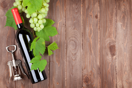 glass of red wine: Bunch of grapes, red wine bottle and corkscrew on wooden table background with copy space