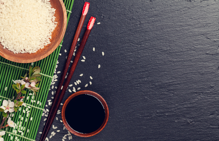 Japanese sushi chopsticks, soy sauce bowl, rice and sakura blossom on black stone background. Top view with copy space. Toned