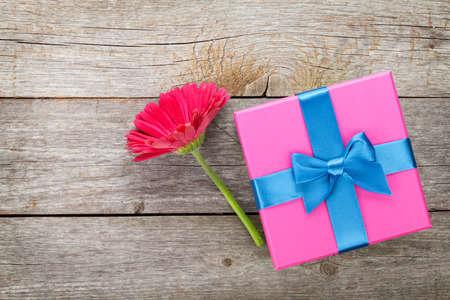 open box: Purple gerbera flower and gift box on wooden table Stock Photo