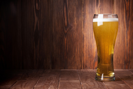 beer bubbles: Lager beer glass on wooden table. View with copy space