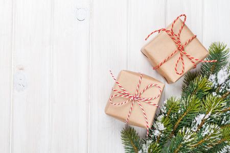 Árbol de abeto de Navidad con nieve y cajas de regalo sobre tabla de madera rústica con espacio de copia Foto de archivo