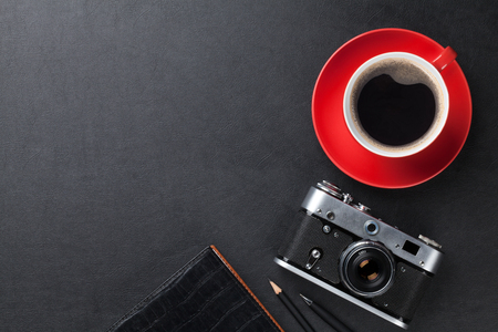 office desk: Office leather desk table with camera, supplies and coffee cup. Top view with copy space Stock Photo
