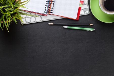 Kancelářské kožené stůl stůl s počítačem, dodávky, šálek a květiny. Pohled shora s kopií vesmíru Reklamní fotografie