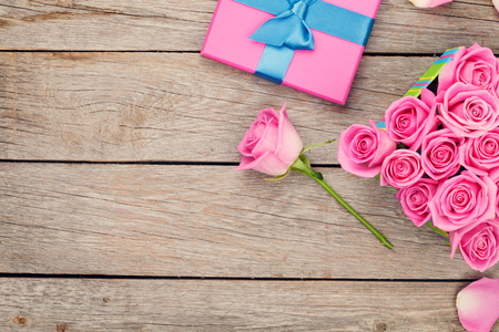 copies: Valentines day background with gift box full of pink roses over wooden table. Top view with copy space