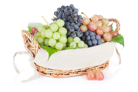 Colorful grapes in basket. Isolated on white background