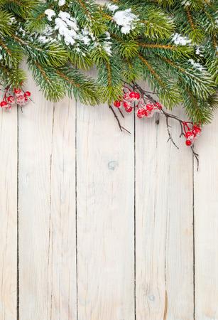 クリスマスもみの木やヒイラギ ベリーと木製の背景。コピー スペースを上から表示します。