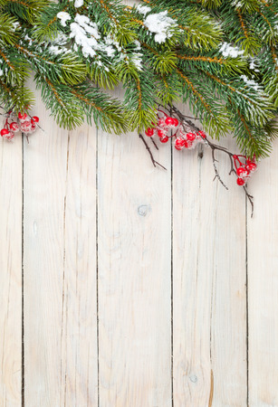 table: Christmas wooden background with fir tree and holly berry. View from above with copy space