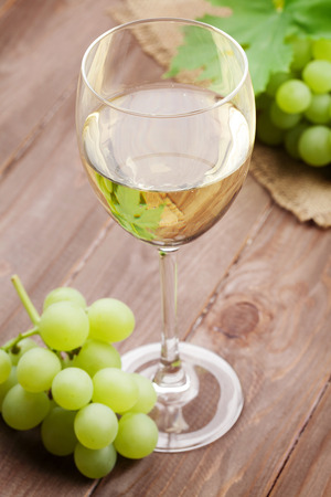 white wine: White wine glass and grapes on wooden table