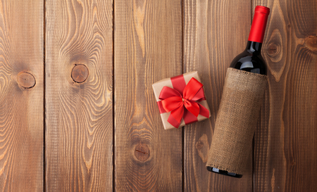 Red wine bottle and valentines day gift box. Over rustic wooden table background with copy space