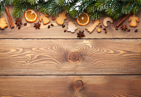 fir tree: Christmas wooden background with snow fir tree, spices, gingerbread cookies and copy space