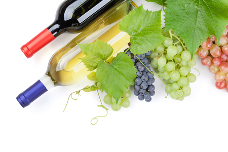 red and white wine: Bunch of red, purple and white grapes and wine bottles. Isolated on white background with copy space Stock Photo