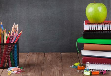 salle de classe: Scolaires et fournitures de bureau sur la table de la classe en face de Blackboard. Voir avec copie espace