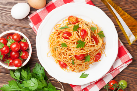 view from the above: Spaghetti pasta with tomatoes and parsley on wooden table. Top view Stock Photo