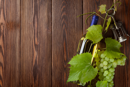 grapes wine: Bunch of grapes, white wine bottle and corkscrew on wooden table background with copy space Stock Photo