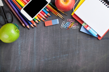 teaching crayons: School and office supplies on blackboard background. Top view with copy space