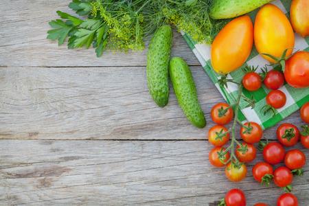 Verse rijpe groenten en kruiden op de tuintafel. Bovenaanzicht met een kopie ruimte