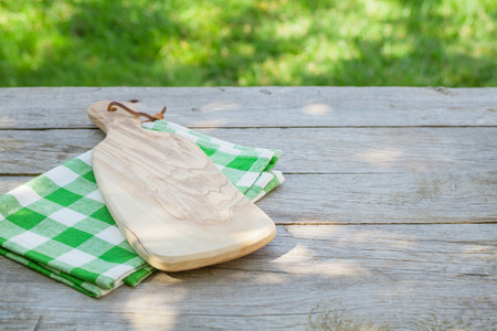 cutting board: Empty wooden garden table with cutting board over tablecloth with green sunny bokeh background