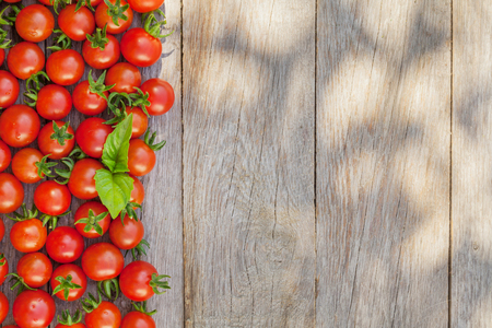 Ripe cherry tomatoes texture and basil leaves on wooden table. Top view with copy space