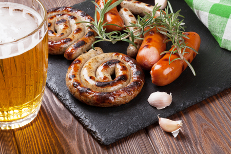 barbecue: Grilled sausages and beer mug on wooden table Stock Photo