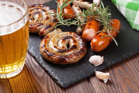 comida alemana: Salchichas a la parrilla y jarra de cerveza en la mesa de madera