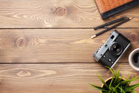 Fotoaparát a zásoby na kancelářské dřevěné desce stolu. Pohled shora s kopií vesmíru Reklamní fotografie