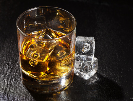 dark glasses: Glass of whiskey with ice on black stone table with copy space