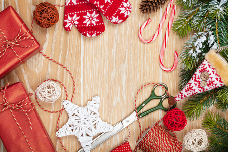 paper roll: Christmas presents wrapping and snow fir tree over wooden table background with copy space