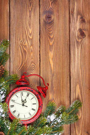 12 month old: Christmas wooden background with clock, snow fir tree and copy space Stock Photo