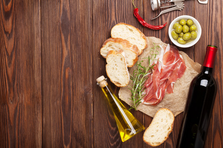 Prosciutto, wine, olives, parmesan and olive oil on wooden table. Top view with copy space Stockfoto