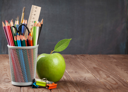 salon de clases: Escuela y útiles de oficina en la mesa de clase delante de la pizarra. Ver con copia espacio