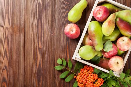Peren en appels in een houten doos op tafel. Bovenaanzicht met een kopie ruimte Stockfoto