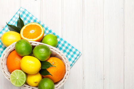 fruits in a basket: Citrus fruits in basket. Oranges, limes and lemons. Over wooden table background with copy space