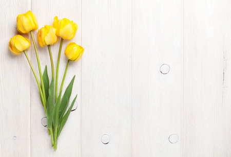 flower designs: Yellow tulips over wooden table background with copy space