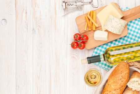 queso blanco: Vino blanco, queso y pan en blanco de madera fondo de la tabla. Vista superior con espacio de copia