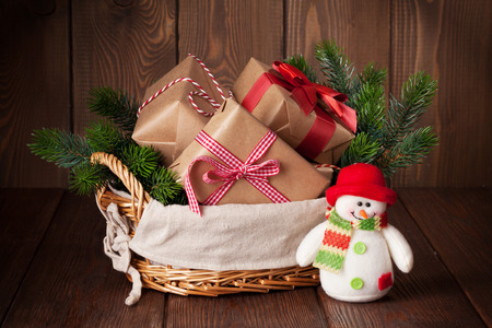 Christmas gift boxes and fir tree in basket with snowman toy Archivio Fotografico