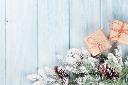 wood box: Christmas wooden background with snow fir tree and gift boxes Stock Photo