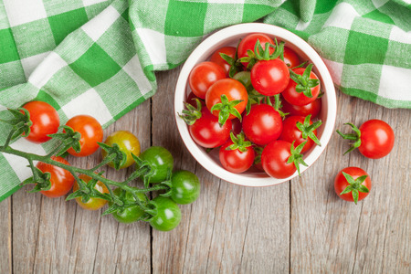 Cherry tomatoes bowl on wooden table. Top view Stockfoto