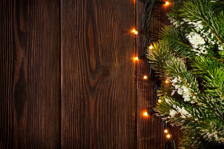 snow and trees: Christmas tree branch and lights on wooden background. View with copy space Stock Photo