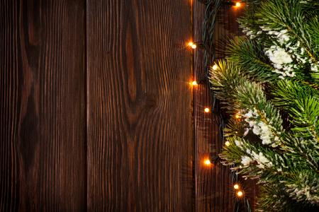 Rama de un árbol de Navidad y luces en el fondo de madera. Ver con copia espacio