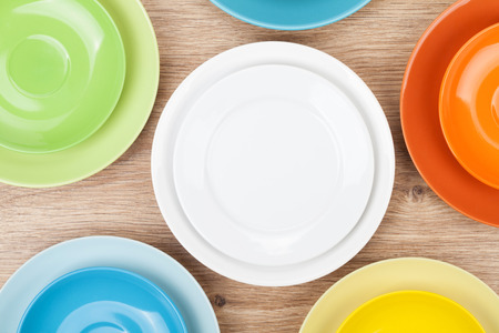 saucers: Colorful plates and saucers over wooden table background. View from above