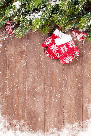 snow tree: Christmas wooden background with snow fir tree and mittens