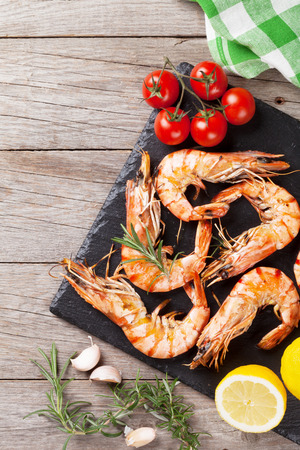Grilled shrimps on stone plate over wooden table. Top view with copy space Stockfoto