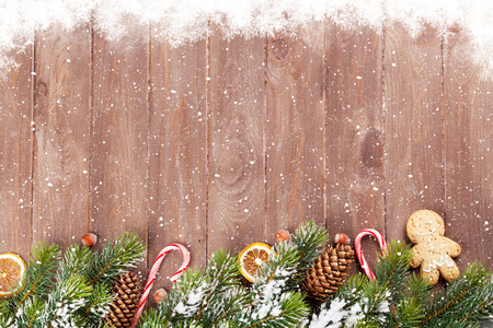Christmas wooden background with snow fir tree and holiday decor