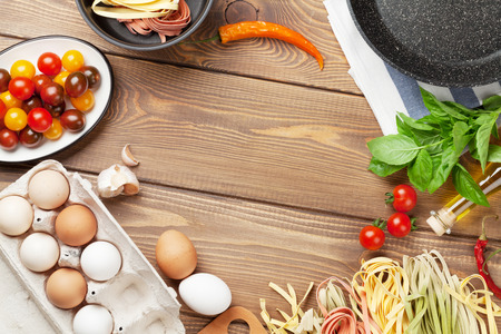 Pasta cooking ingredients and utensils on wooden table. Top view with copy space Фото со стока
