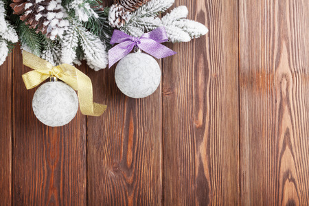 christmas baubles: Christmas wooden background with snow firtree and baubles. View with copy space Stock Photo