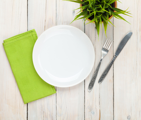 table setting: Empty plate and silverware over white wooden table background. View from above with copy space Stock Photo