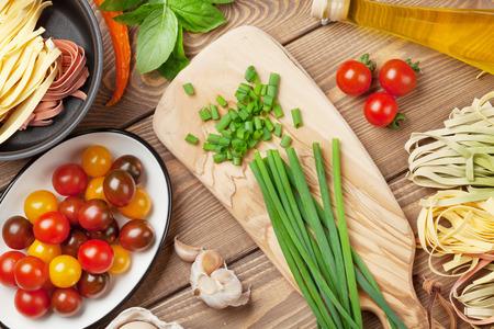 Pasta koken ingrediënten en gebruiksvoorwerpen op houten tafel. Bovenaanzicht Stockfoto