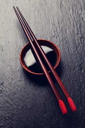 Japanese sushi chopsticks over soy sauce bowl on black stone background