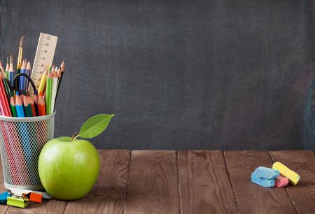 tablero: Escuela y útiles de oficina en la mesa de clase delante de la pizarra. Ver con copia espacio