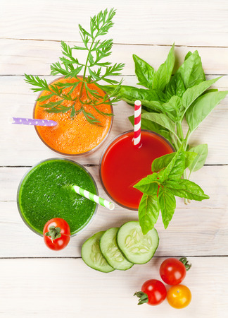 sano: Batido de verduras frescas en la mesa de madera. Tomate, pepino, zanahoria. Vista superior